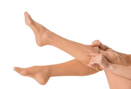 Beautiful young woman putting on tights against white background 版權商用圖片