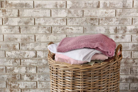 Wicker basket with clean towels in room