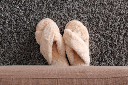 Pair of soft slippers on carpet in room
