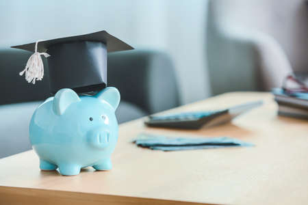 Piggy bank with graduation cap on table in room