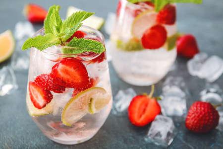 Glass of fresh strawberry mojito on dark background
