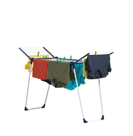 Clean clothes hanging on dryer against white background