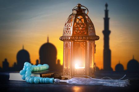 Muslim lamp, tasbih and Koran on table at sunset Reklamní fotografie