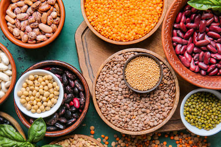 Different raw legumes with spices on color background