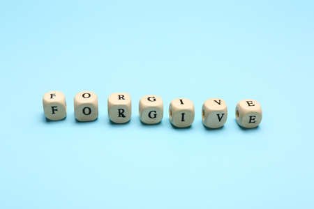 Cubes with word FORGIVE on color background Imagens