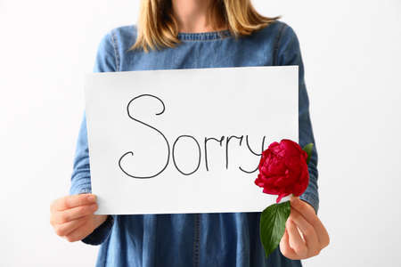 Woman holding paper with word SORRY on white background, closeup Banque d'images