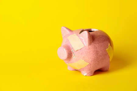 Broken patched piggy bank on color background Stock Photo