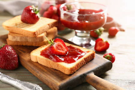 Bread with tasty strawberry jam on table Stock fotó