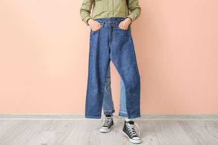 Beautiful young woman in jeans near color wall Zdjęcie Seryjne
