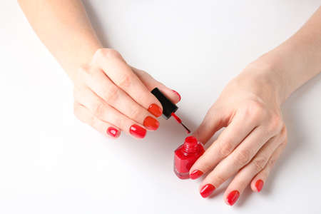 Hands with nail polish on white background