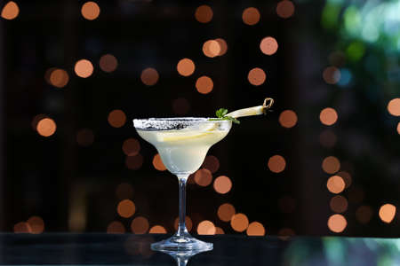 Glass of fresh martini on dark background