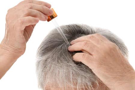Senior woman using serum for hair loss treatment on white background, closeup