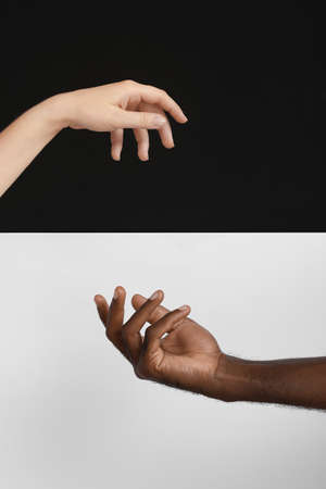 Hands of Caucasian woman and African-American man on black and white background. Racism concept Imagens