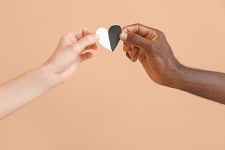 Hands of Caucasian woman and African-American man with heart on color background. Racism concept