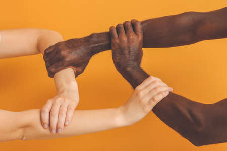 Caucasian woman and African-American man holding hands together on color background. Racism concept