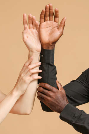 Caucasian woman and African-American man holding hands together on color background. Racism concept Imagens