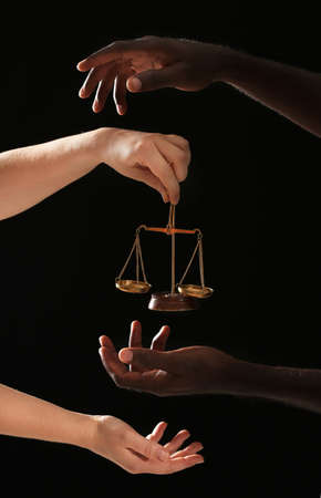 Hands of Caucasian woman and African-American man with scales of justice on dark background. Racism concept