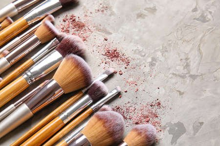 Set of makeup brushes and cosmetics on light background