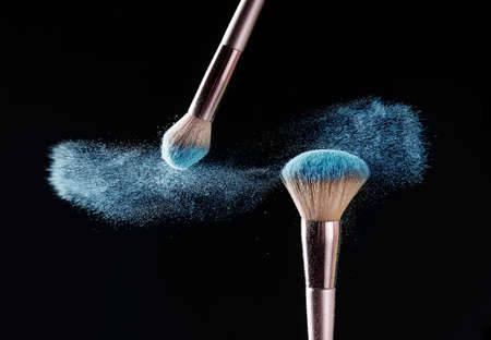 Makeup brushes and burst of cosmetics on dark background