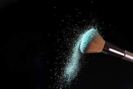 Makeup brush and burst of cosmetics on dark background Standard-Bild