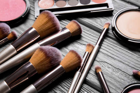Set of makeup brushes and cosmetics on wooden background, closeup