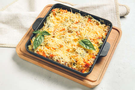 Baking dish with tasty rice casserole on white background