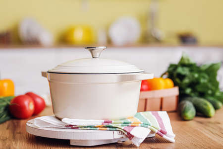 Cooking pot and products on table in kitchen