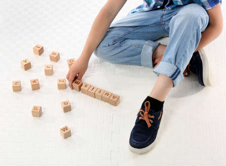 Little boy with autistic disorder playing with cubes on white background