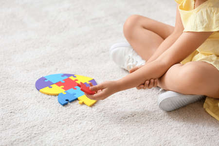 Little girl with autistic disorder doing puzzle at home
