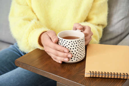 Woman with cup of tea resting on sofa at home