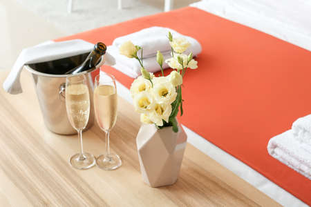 Glasses of champagne and ice bucket on table in honeymoon room Foto de archivo
