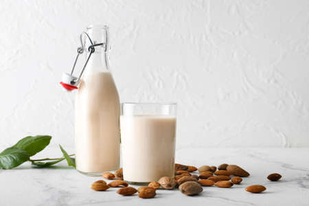 Bottle and glass with tasty almond milk on table