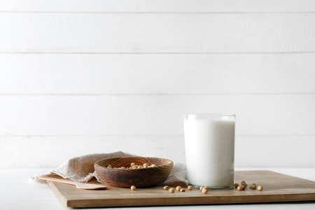 Glass of tasty soy milk on wooden board