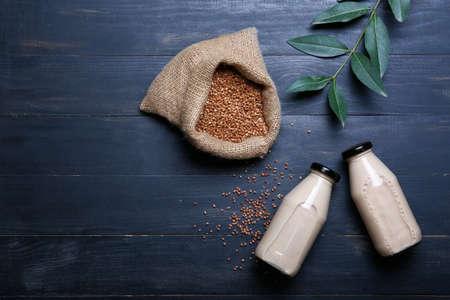 Bottles of buckwheat milk on wooden background Foto de archivo