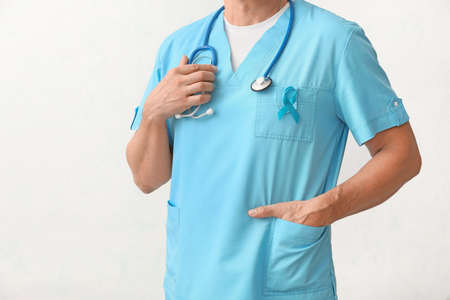 Male doctor with blue ribbon on light background. Prostate cancer awareness concept Stock Photo
