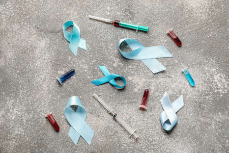 Blue ribbons, medication and blood sample on gray background. Prostate cancer awareness concept