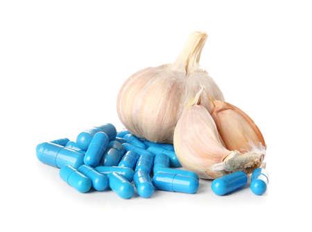 Fresh garlic with pills on white background