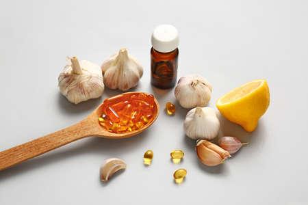 Fresh garlic with lemon and pills on light background