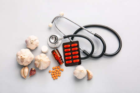 Fresh garlic with pills and stethoscope on light background