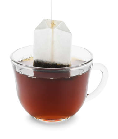 Taking tea bag out of glass cup with hot beverage on white background Foto de archivo