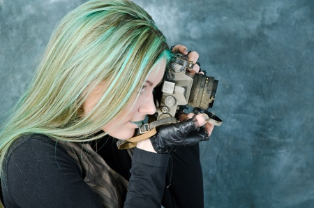 Photo session of the pretty young blonde girl with green hair in the steampunk style with photo camera photo