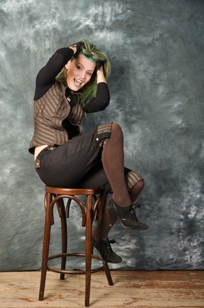 Pretty young blonde girl with green hair in the steampunk style demonstrates the fear photo
