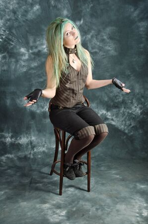 Pretty young blonde girl with green hair in the steampunk style demonstrates that she was not succeeded in something