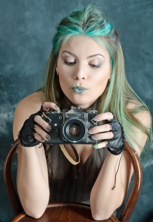 Photo session of the pretty young blonde girl with green hair in the steampunk style with photo camera
