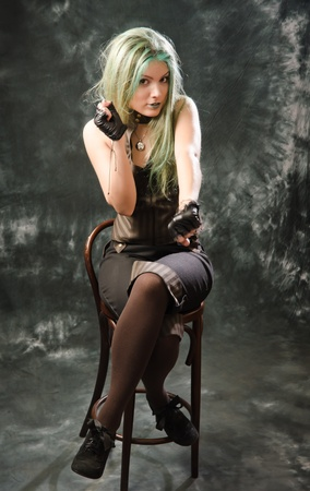 Photo session of the pretty young blonde girl with green hair in the steampunk style photo