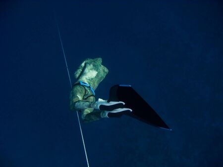 Freediver makes deep dive by line near the coral reef in Blue Hole, Dahab, Egypt
