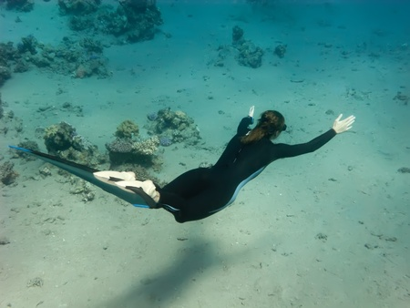 The freediver girl swims along sand Red sea bottom
