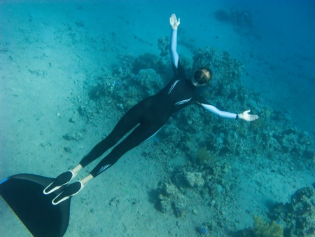 Beautiful freediver girl poses near the coral reef and sand bottom of the Red Sea