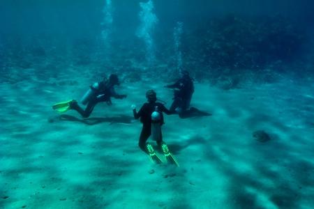 Drie duikers zitten op de Rode Zee bodem zand en training