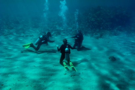 exhalation: Three divers are sitting on the Red Sea bottom sand and training